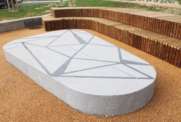 Deler av parken senkes ned i terrenget og omgis av et amfi med brede sitteflater. En stor granittstein danner sentrum i amfiet og inviterer til aktivitet. Foto: Asplan Viak