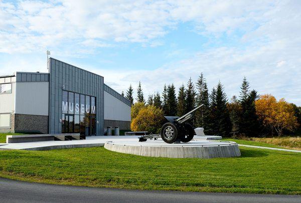 <p>Museumsbygningen med forplass og landskap. Museet er etablert i en ombygd industribygning. Museets forplass og anlegget er presist, enkelt og nøkternt formgitt, inspirert av kystfortets rå og funksjonelle form. Foto: Asplan Viak</p>